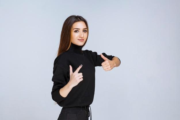 Mulher de camisa preta, mostrando sinal positivo com a mão.