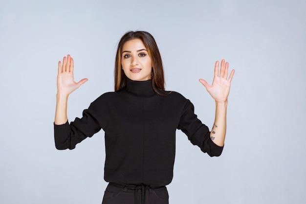 Mulher de camisa preta, parando e evitando algo.