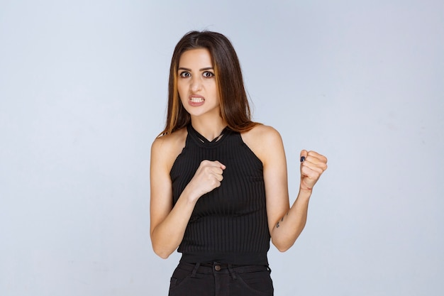 Mulher de camisa preta parece agressiva e chateada.