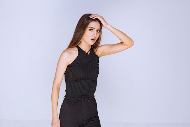 Mulher de camisa preta parecendo triste e nervosa.