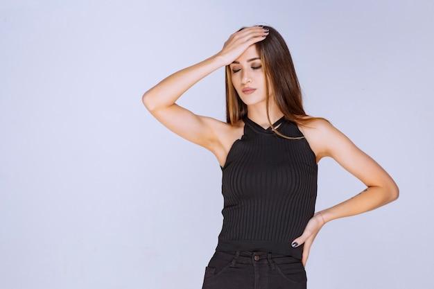Mulher de camisa preta se sentindo triste ou com dor de cabeça.