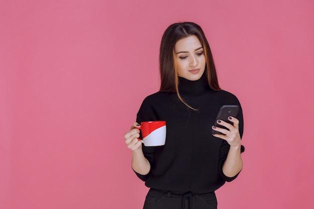 Mulher de camisa preta segurando uma xícara de café e falando ao telefone.