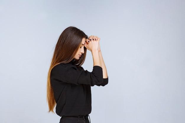 Mulher de camisa preta, unindo as mãos e orando.