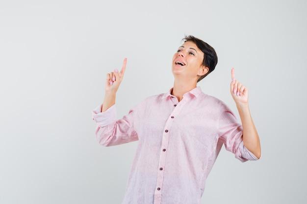 Mulher de camisa rosa apontando para cima e olhando agradecida, vista frontal.