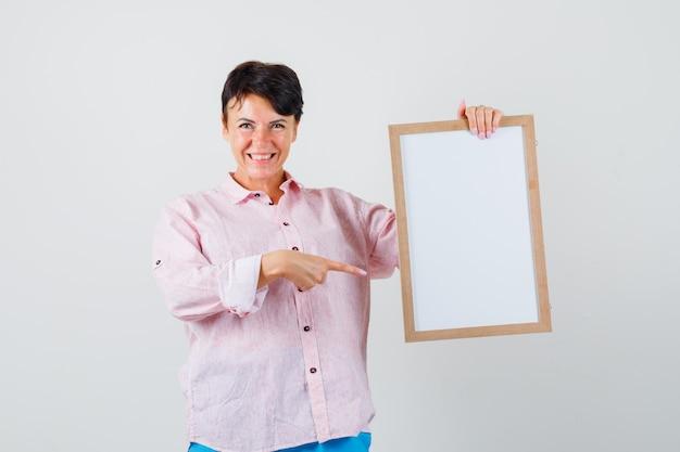 Mulher de camisa rosa, calça apontando para uma moldura vazia e olhando alegre, vista frontal.