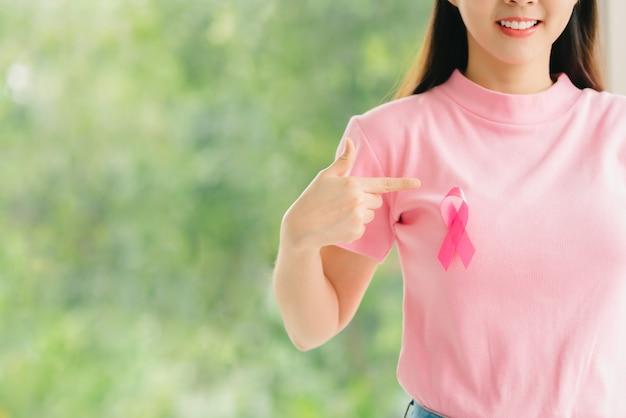 Mulher de camisa rosa com fita de conscientização de câncer de mama