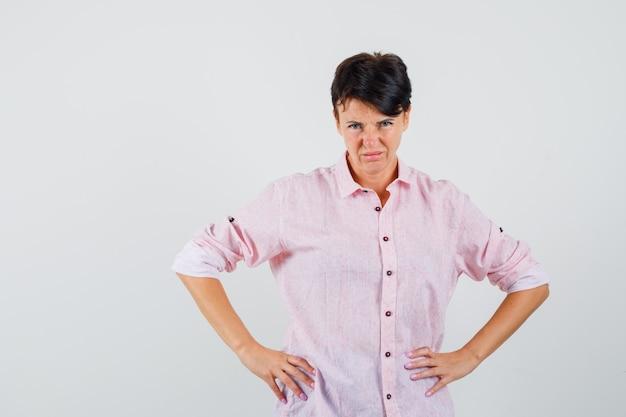 Mulher de camisa rosa de mãos dadas na cintura e olhando desconfiada, vista frontal.