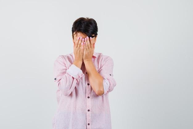 Mulher de camisa rosa de mãos dadas no rosto e parecendo aflita, vista frontal.