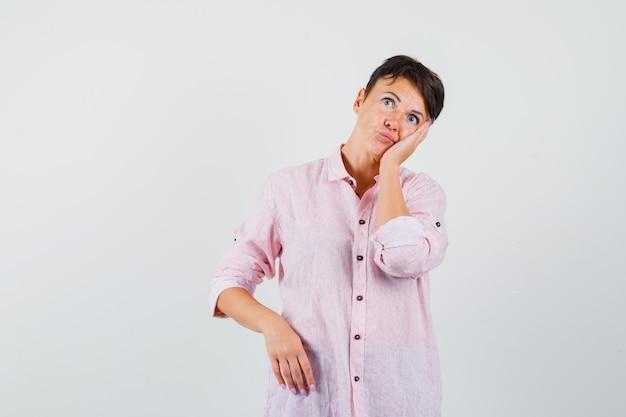 Mulher de camisa rosa inclinando a bochecha na palma da mão levantada e parecendo um sonho, vista frontal