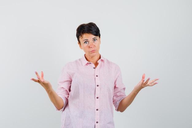 Mulher de camisa rosa, mostrando um gesto desamparado e parecendo confusa, vista frontal.
