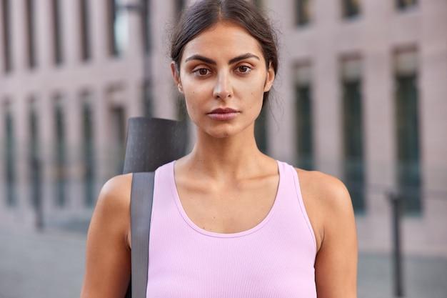 Mulher de camisa rosa olha diretamente para a câmera e carrega karemat em poses de ombro na cidade turva