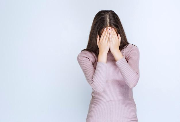 Mulher de camisa roxa está com sono ou com dor de cabeça.