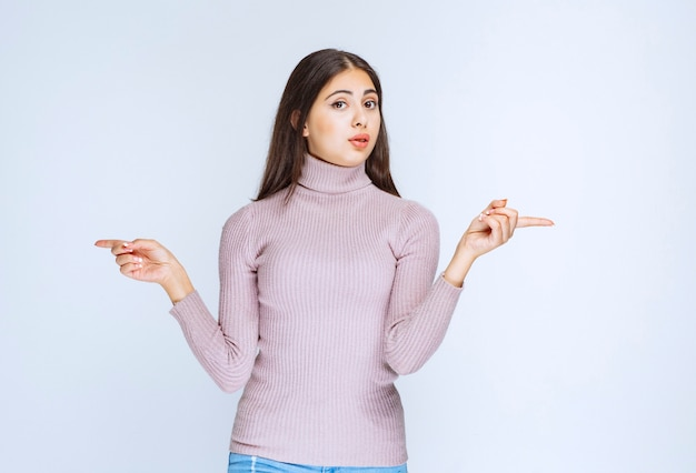Mulher de camisa roxa mostrando algo à esquerda.