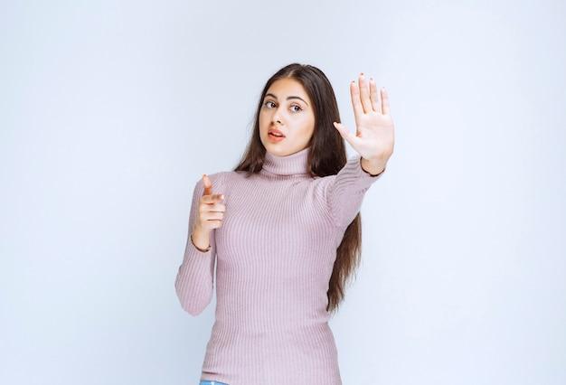 Mulher de camisa roxa, parando algo com as mãos.