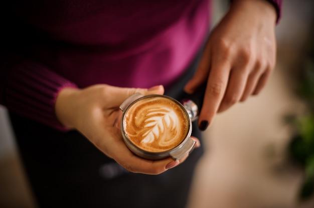 Mulher de camisa roxa segurando um temperamento com uma bela arte de café com leite