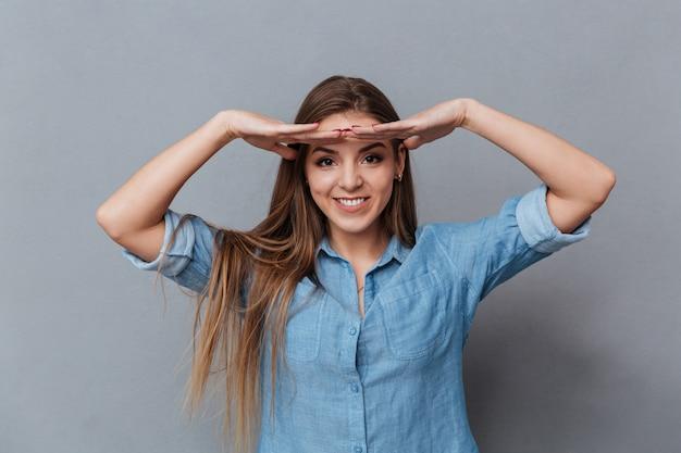 Mulher de camisa, segurando as mãos na testa