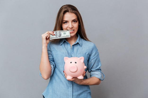 Mulher de camisa segurando moneybox e dinheiro nas mãos