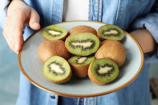 Mulher de camisa, segurando o prato de kiwi maduro
