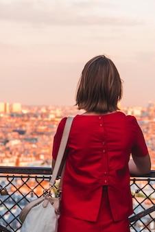 Mulher de camisa vermelha e calça vermelha encostada na cerca de metal