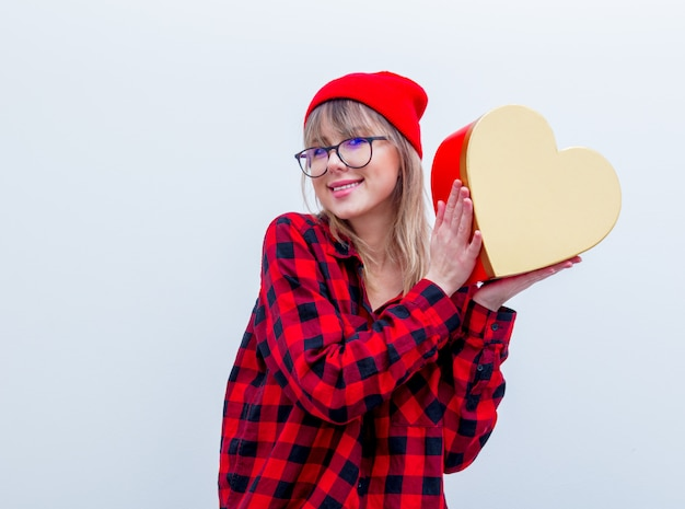 Mulher de camisa vermelha e chapéu segurando a caixa de presente de forma de coração