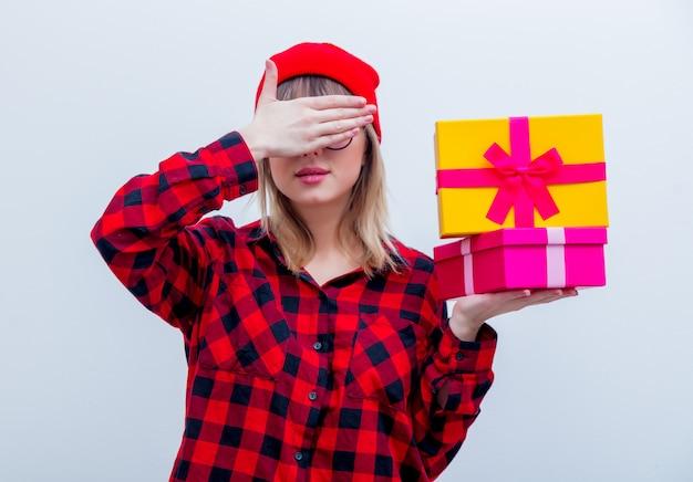 Mulher de camisa vermelha e chapéu segurando caixas de presente de feriado
