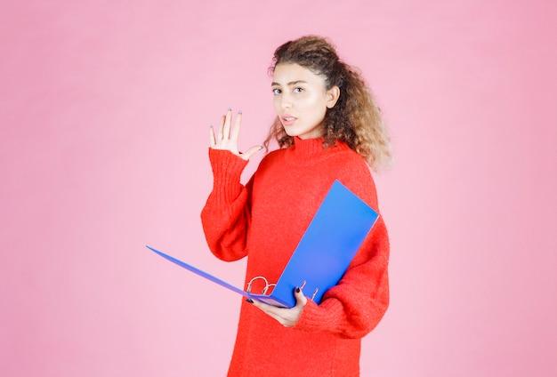 Mulher de camisa vermelha, parando e impedindo algo.