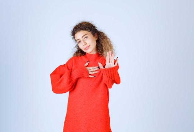 Mulher de camisa vermelha, parando e impedindo algo. Foto gratuita
