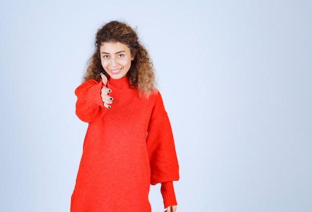 Mulher de camisa vermelha percebendo alguém à frente e enviando energia positiva.