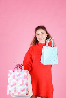 Mulher de camisa vermelha, segurando várias sacolas coloridas.