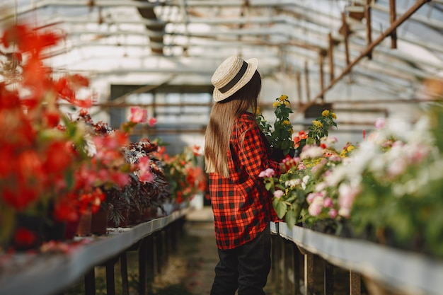 Mulher de camisa vermelha. trabalhador com potes de flores. filha com plantas
