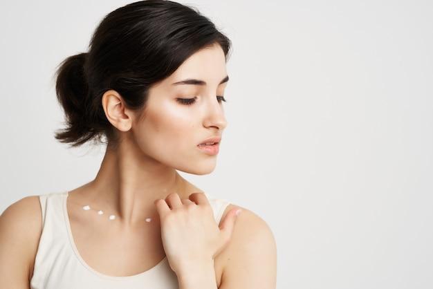 Mulher de camiseta branca aplica creme no pescoço dermatologia de pele limpa