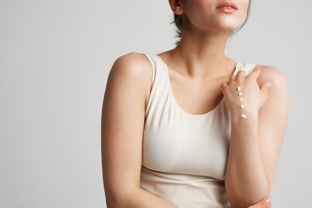 Mulher de camiseta branca aplicar creme nas mãos, fundo claro de cuidados com a pele