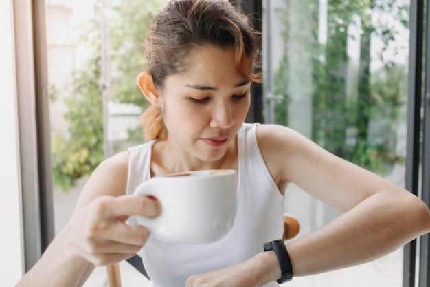 Mulher de camiseta branca bebendo café e olhando para o relógio