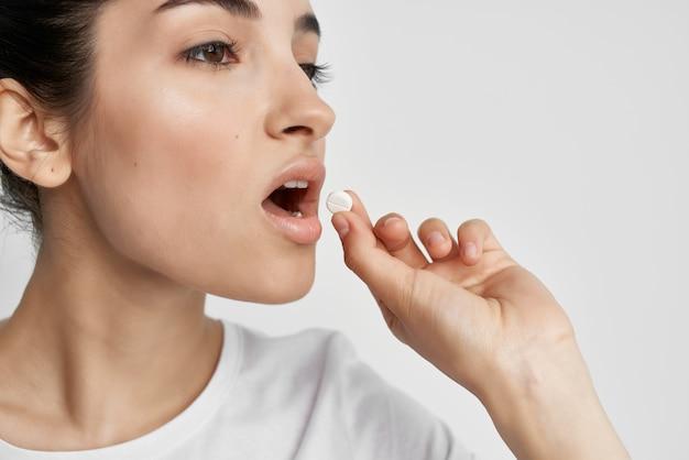 Mulher de camiseta branca com comprimidos nas mãos, remédio para problemas de saúde