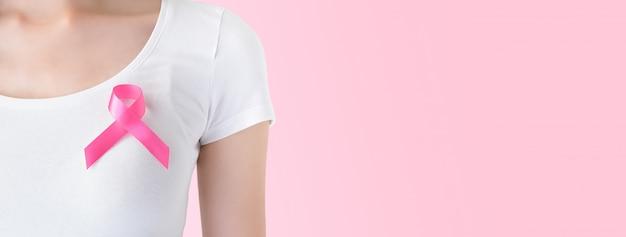 Mulher de camiseta branca com fita rosa no peito, apoiando o símbolo da campanha de conscientização do câncer de mama em outubro