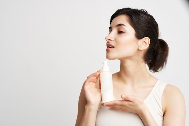 Mulher de camiseta branca com loção, cosméticos para pele saudável