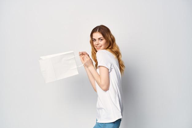 Mulher de camiseta branca com pacotes nas mãos, compras de entretenimento de estilo de vida. foto de alta qualidade