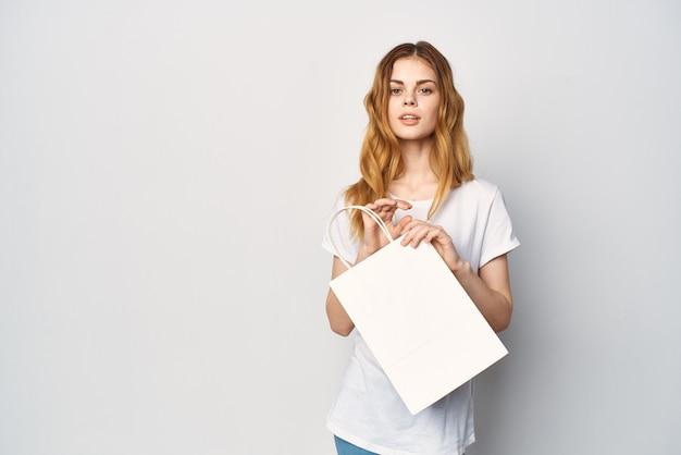 Mulher de camiseta branca com pacotes nas mãos, compras, entretenimento, estilo de vida