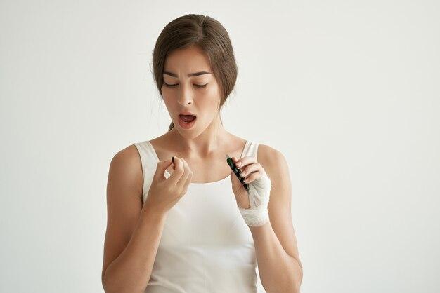 Mulher de camiseta branca com remédios para as mãos enfaixados