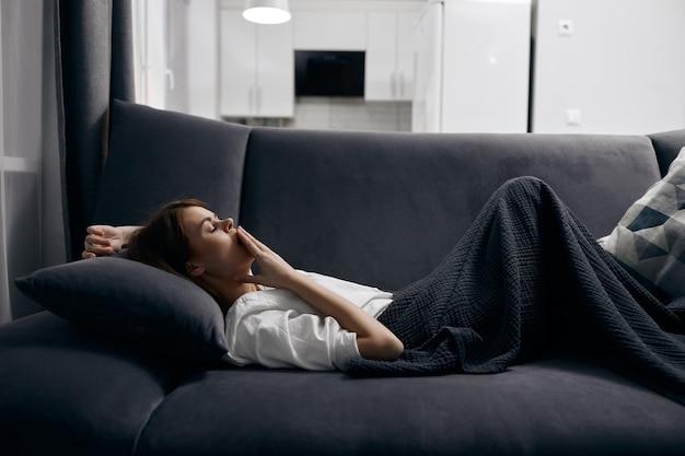 Mulher de camiseta branca descansando deitada no sofá dentro de casa