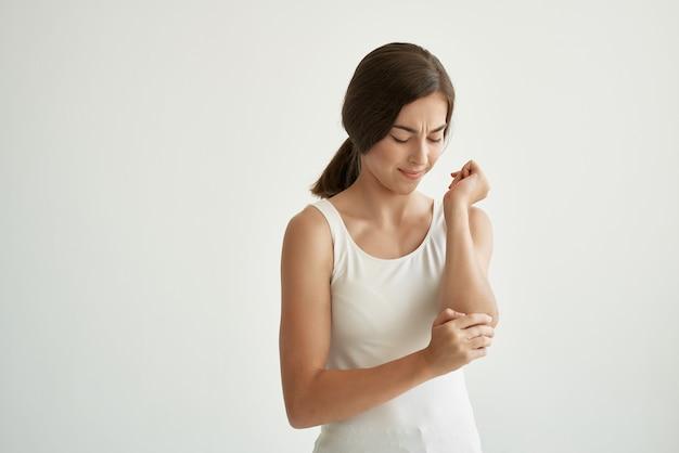 Mulher de camiseta branca, dor crônica, compostos de problemas de saúde