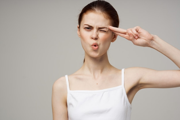 Mulher de camiseta branca dor de cabeça problemas de saúde estresse isolado fundo