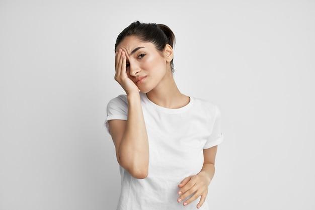 Mulher de camiseta branca, dor de cabeça, problemas de saúde