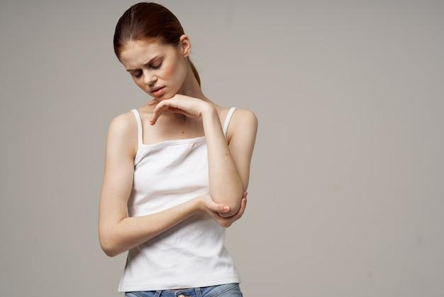 Mulher de camiseta branca dor no cotovelo artrite doença crônica fundo claro