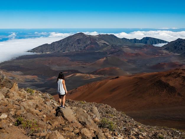Mulher de camiseta branca e bermuda azul em pé na montanha de pedra marrom