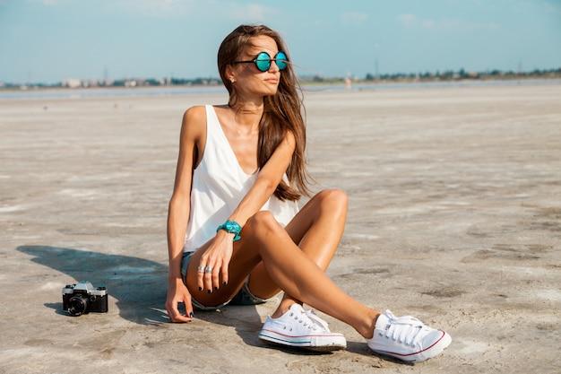 Mulher de camiseta branca e elegantes óculos de sol posando na praia.
