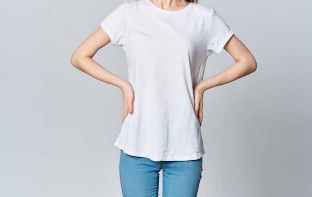 Mulher de camiseta branca e jeans gesticulando com as mãos cortadas vista da modelo