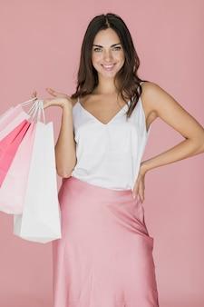 Mulher de camiseta branca e saia rosa com redes de compras