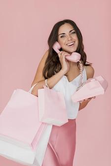 Mulher de camiseta branca e saia rosa, falando ao telefone