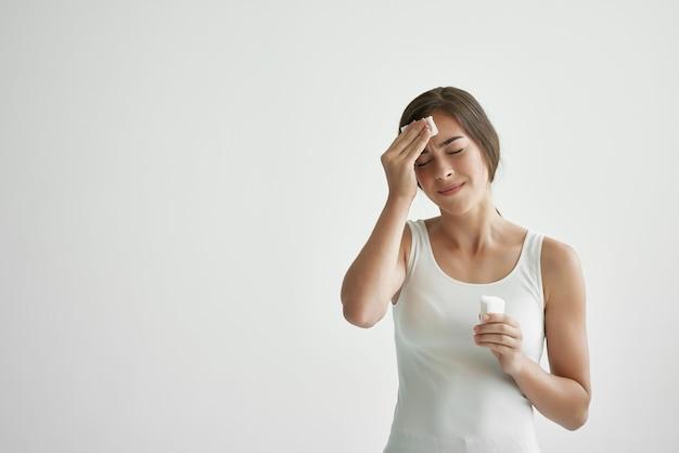 Mulher de camiseta branca enxuga a testa com um lenço de febre suor resfriado